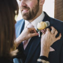 Groom having buttonhole put on